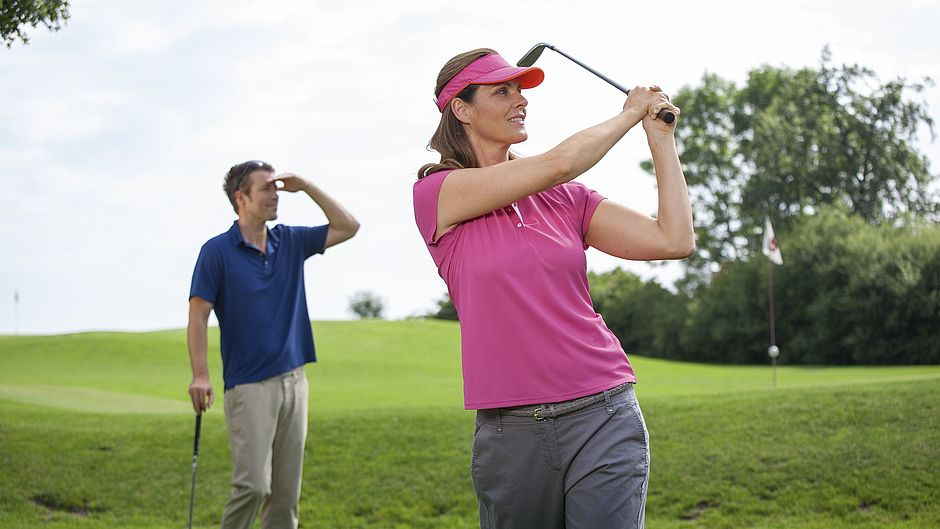 Woman playing golf in pink polo shirt